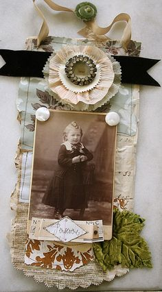 Antique sepia-toned photo tag wrapped in laces, old book text, ribbons, buttons, jewelry, and various beauties.  To hang on a door knob, perhaps?