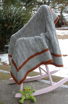 """A highly textured baby blanket knit up quickly in superwash bulky yarn and large needles. Great for boys because there is no lace! The center section is worked back and forth and then bound off. The slip stitch tweed border is worked in-the-round on stitches that have been picked up around the edge of the blanket on a long circular needle (60"""" cable). Pick a light shade for your Main Color (so the lovely textures will show up nicely), and go for a bright/wild color for the contrasti..."""