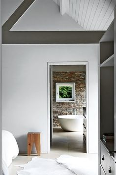 Minimalist barn bedroom with en suite bathroom in Bedroom Decoration Ideas. Pale grey bedroom and en suite with monochrome decoration scheme and rustic accents.