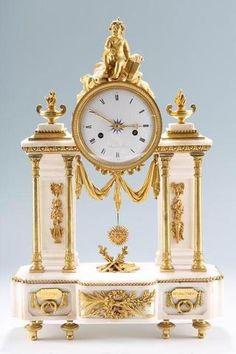 Pendule portique en marbre blanc et bronze doré - elle est formée de 4 colonnettes avec 2 pilastres entourant le cadran et surmonté d'un amour - décor de pots flammés drapés, attributs - la base à décrochement avec 2 plaques marquées Ciceron et Demosthn - L'ensemble reposant sur des pieds toupies - le cadran signé Thiery à Paris - Epoque Louis XVI Long. 39 cm et haut. 52 cm