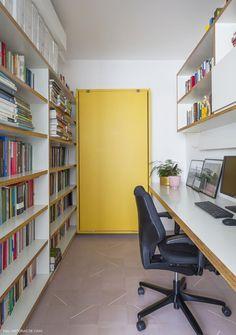Home office tem piso de ladrilho hidráulico e cama retrátil para hóspedes.