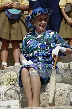 Queen Elizabeth II, wearing a blue multi-coloured dress designed by John Anderson, and a hat by milliner Philip Somerville, sitting laughing during a visit to Cyprus, 21 October 1993. The Queen is on an official visit to Cyprus, in her capacity as Head of the Commonwealth, to attend the 13th Commonwealth Heads of Government Meeting.