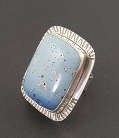 A beautiful Leland blue cabochon is bezel set in a handmade sterling silver setting. The back plate and ring band have been hand stamped for added texture. The entire ring is then oxidized to bring out the detail. This ring measures approx 1.5 long, is one of a kind and ready to ship and is a size 8. PAYMENT PLANS ARE AVAILABLE ON ALL ITEMS UPON REQUEST! CONTACT ME FOR MORE INFO Some of my rings can not be resized. Some can be resized for a small fee. If you would like to know if a ring can…