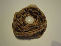 Vintage style tan and plum floral fabric rosette with button (button may vary) comes mounted on a covered alligator clip to be worn by all ages!! Only $6.50