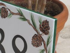 These house numbers are perfect for a cozy cabin or forest home . Tile House Numbers PINE CONES Address Plaque by cmbstudio on Etsy . Tile House Numbers, Address Plaque, Forest House, Cozy Cabin, Christmas Decorations, Holiday Decor, Christmas Baby, Christmas Inspiration, Pine Cones
