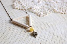 collier tout simple avec de la chaîne bille en laiton. Le pendentif est un triangle composé e trois perles tubes écrus, et d'où pendent une perle jaun