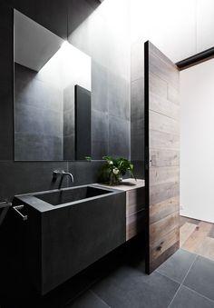 Solid wood paneling, dark gray wall tiles, washbasin design matching rectangular mirror