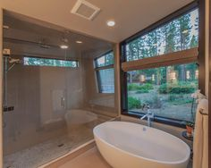 Clean lines and clean surfaces, this modern mountain bathroom keeps decor simple. A window right over the tub provides natural light and an outdoor view, but can be covered when privacy is needed.