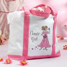 """Flower Girl Tote Bag made of white nylon canvas. The bottom is pink with pink trim and pink handles. The front features an embroidered design of a flower girl holding a flower basket with a butterfly on her hand. The words """"Flower Girl"""" in printed in black to the side of the image."""