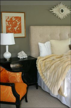 orange elegant bedroom design with cream ivory tufted upholstered headboard bed with pops of orange! Love the contrast of the black wood nightstand and white gourd lamp! Upholstered orange silk chair and art is fabulous! Gray paint wall color. Love the luxurious faux mink throw as well. orange black gray white cream ivory bedroom space colors.