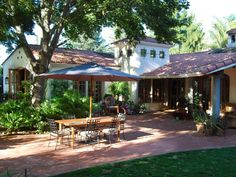 Lush landscaping and a generous red brick patio distinguish this Southwestern style home and backyard.