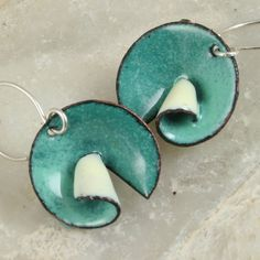Here is something different for me. I took discs of cooper cut them and then curled back a portion of the copper, all shaped by hand. I enameled the front and back different colors carrying the back portion as it curls to the front This pair is Sea Green/Aqua and Cream. All are fired on the back for stability. Never accept enameling that is not enameled on both sides. The ear wires are hand crafted of 20 gauge sterling silver.  Photos are magnified. Be sure to check measurements:  Total ...