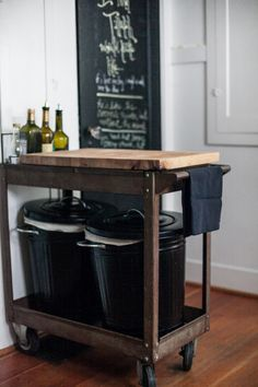thrifted repurposed cart on casters w/ IKEA butcher top, trash & recycling bins, & chalkboard door