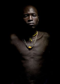 Surma warrior with scarifications - Ethiopia by Eric Lafforgue, via Flickr    Men , like women, also have some scarifications on their body. It is a beauty sign for women , for men, it tells the fights he made.