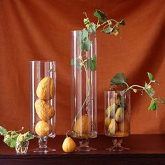 Gather gourds in cylindrical vases to bring autumn to a tabletop or mantel. Use containers of different sizes to stack gourds in varying amounts. To give each display a vibrant touch, add a length of fresh pumpkin vine from the garden.