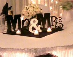 Our head table- we wanted to be a little different and decided to do this:) ...we bought the letters at Michaels and glued them to a piece of flat wood using wood glue. $20 total cost
