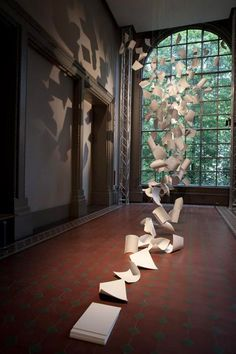 """Installation Art...'A Gust of Wind' by Pauls Cocksedge, an installation of 300 sheets of corian engraved with the words """"Idea Tray"""" and a series number and suspended like sheets of falling paper, Victoria and Albert Museum."""