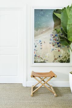 Living room corner with a small stool and large aerial beach photography art framed in simple white frame