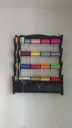 I bought a gun rack from a nearby thrift shop, painted it black and used black wooden rods to hang across the rack for my ribbons.