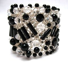 """Looks like Chanel--Black Onyx & Crystal with Black Onyx edging. Silver wire.  Length: 7¼""""  Width: 2""""  300- US$  The artist makes a frame of woven wire and then ´sews´ random beads onto the frame. Some of them are quite wide and very dramatic; others are narrower and have a more delicate quality. In either case, they have a vintage feel. The clasps are quite easy to use and hold very well."""