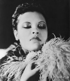 Billie Holiday poses for a studio portrait in 1939 in the United States. Description from jazzinphoto.wordpress.com. I searched for this on bing.com/images