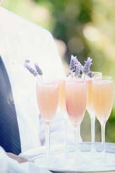 A blushing bride signature cocktail made of peach schnapps, grenadine, and champagne with a sprig of fragrant lavender | Brides.com