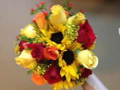 Sunflower, assorted roses, hypericum and tinted wax flower.