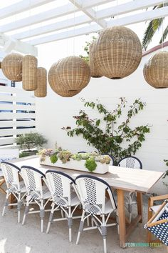 Outdoor dining space with woven basket pendant lights, navy blue and and white bistro chairs, wood outdoor table, succulent planter and white pergola. Travel Files: Montage Laguna Beach & Southern California - Life On Virginia Street
