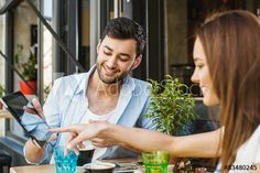 Young couple in sidewalk cafe and using digita tablet.