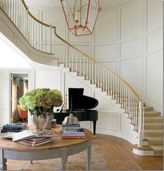 Image via Carol Glasser Interior Design This foyer could have taken on many different looks with the sweeping curved staircase and the paneled walls. The predictable would have been to go formal, but the sisal Foyer Staircase, Entryway Stairs, Curved Staircase, Entry Hallway, Staircase Design, Entryway Decor, Winding Staircase, Spiral Staircases, South Shore Decorating