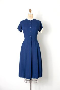 vintage late 1940s / early 1950s dress. navy blue rayon with ivory ribbed cotton knit trim around the neck and sleeves. such a simple and beautiful dress with the best tiny round buttons (look at the closeup pic!!). button up bodice, bust darts and flowing pleated skirt. belt loops but missing original belt. a great example of beautiful simplicity and that keen attention to detail that makes vintage the best!  L A B E L n/a  M E A S U R E M E N T S bust 34 waist 26.5 hips up to 45 l...