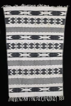 Africa   Skirt/wrapper from the Igbo people of Nigeria   20th century   Cotton ~ white and dark blue textile; embroidered decorations include diamonds among other geometric shapes; longer edges have dark blue border; shorter edges have white and dark blue fringe