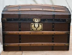 "An all original wooden French Fashion domed trunk featuring wooden and metal trim , metal handles and lift-out Tray. The inside of the trunk is  off white and blue striped original paper, blue silk ribbons at the lid and  original paper label ARTICLES DE VOYAGE SURAULT-COULEMBIER,  PARIS, 93 boul.Hausmann. 16 1/4"" long, 10"" wide, 10"" high."