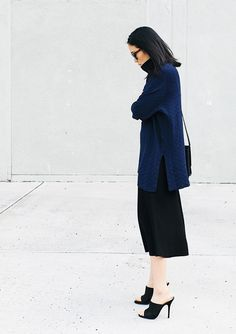 A navy turtleneck sweater is worn with a black pencil skirt and black mules.