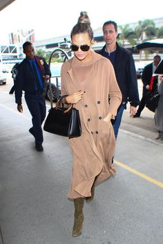 Pin for Later: See All of Chrissy Teigen's Best Maternity Looks Right Here  Chrissy covered up in a neutral buttoned coat for a flight, carrying her black leather satchel and wearing oversize sunglasses.