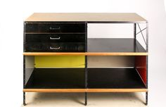 Charles (American, 1907-1978) and Ray Eames (American, 1912–1988) for Herman Miller mid century modern ESU 200-N, circa 1950, with rectangular top above three black painted front pull out drawers in upper left, shelf storage in remaining three quadrants supported on black painted metal frame with stretcher shelf.
