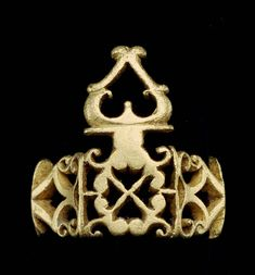 """A gold ring with openwork (or pierced work; opus interrasile) composed of a design of juxtaposed peltae and scroll work. At the front the scrollwork is organized in a square field with a central """"chi."""" From this rises an """"omega"""" and a """"lambda"""" mounted on a kind of pedestal. At the back of the ring is a solid, quasi-square panel set with a two-layered (white and honey-colored) stone."""
