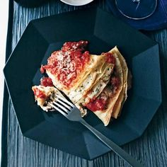 Crespelle with Ricotta and Marinara | In this recipe, adapted from Wine Bar Food by Tony Mantuano and his wife, Cathy, lush ricotta-filled crêpes bake in a rich marinara sauce.