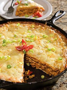Baked Mexican Pie  1 lb ground beef  1  (1.25-oz) pk taco seasoning  2/3  c beef broth  2 T butter  1  med onion, chopped  2  T chopped garlic  1/2  c chopped green onion  1  (4.5-ounce) can chopped green chiles  1  (10.75-oz) can cream of onion soup  1  (10-oz) can enchilada sauce  1  (16-oz) can refried beans  5  (12-inch) flour tortillas  3  c shredded Pepper Jack cheese  Garnish:  sour cream, chopped green onions, chopped tomatoes