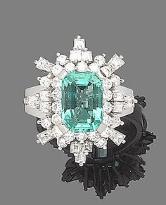 An emerald and diamond ring  The step-cut emerald, within a brilliant, square and tapered baguette-cut diamond surround, to trifurcated shoulders, diamonds approx. 1.55cts total,