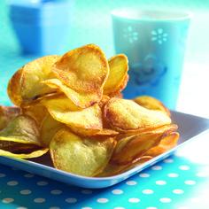 Verdeel de aardappelschijfjes zo over het bakpapier dat ze niet op elkaar liggen. Bestrijk ze met olie en strooi er wat zout op. Laat ze in 15-20 minuten in het midden van de oven goudbruin worden. Draai ze eventueel even om met een keukentang. Serveer er een lekkere dip bij.