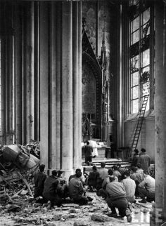 Germany. American soldiers with rifles kneeling to pray amidst bombing rubble in Cologne Cathedral as an Army chaplain holds the first Mass since its bombing on March 2nd, 1945.  Via Catholic Love