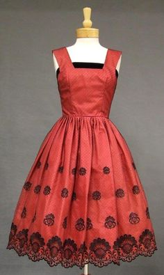 A gorgeous 1950's cocktail dress in black tulle backed in red nylon and lined in watermelon acetate. Fitted bodice with wide straps and a black velvet band along the top edge. Black velvet bow with trailing streamers at the rear. Dress has a semi-full, pleated skirt with black embroidery and a scalloped hem.