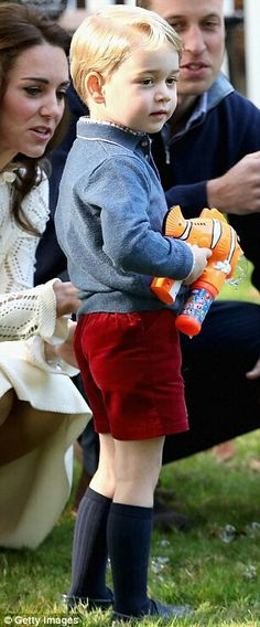 Prince George holds a bubble gun as his parents, the Duke and Duchess of Cambridge look on. Government House children's party. Canada. September 29 2016