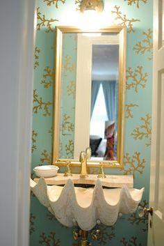 Coral wallpaper & a large shell sink create an avant-garde coastal bath