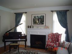 Example that a baby grand piano *can* fit into a very small living room - here in front of one window, tucked into the corner - with a large, comfy wing chair in front of the other window - framing the fireplace. Nice country setting.