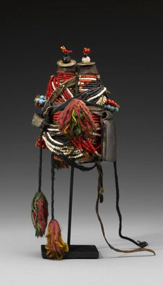 Africa | Twin dolls from the Fali people of Cameroon | Wood, West African coins, red, black, white, blue glass beads, fiber, leather, string || This doll represents desired twins, possibly a male and female. A leather amulet pack offers protection from negative forces and to ensure a healthy and productive life.
