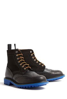 Black suede and leather boots by Mark McNairy New Amsterdam featuring brogue punch and stitch detailing to smooth and textured leather, a suede tongue, blue Commando soles, yellow and burgundy laces through silver eyelets and a black storm welt. This item runs true to size.    Leather upper, leather inner, rubber sole.