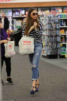 Her bag's full: The Modern Family star wore a blue and white striped T-shirt with ripped jeans and blue high-heeled platform sandals as she went pretty much unnoticed by shoppers
