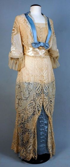 Two-piece dress, ca. 1912, cream lace over pale blue silk. Bodice and overskirt have cutwork, embroidery, and lace insertion, trimmed in silk. Skirt has row of faux silk buttons in front. Slightly longer length in back.